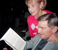 Photo Caption: Aaron, who is faced with age-related vision loss, reads from a JBI Large Print Haggadah as his wife looks on.