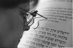 Photo Caption: A woman reading from a JBI Large Print text.
