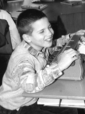 Photo Caption: Tomas, a young boy in Hungary, using a Perkins Braille typewriter.